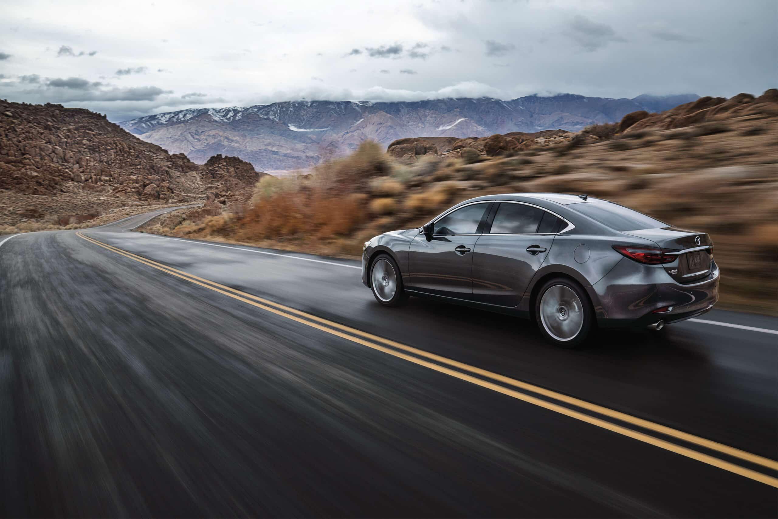 Vue arrière de la Mazda6 2020 grise sur route pittoresque