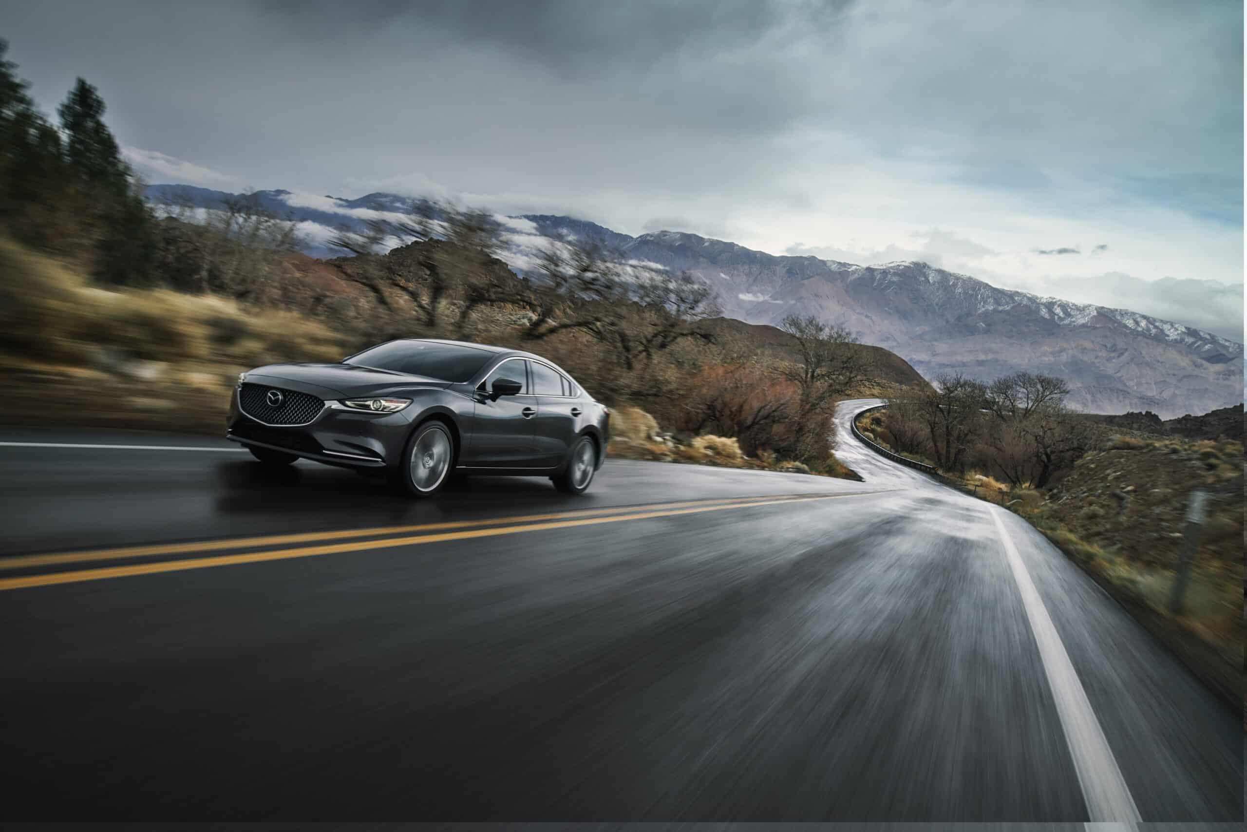 Devant de la Mazda6 2020 grise sur route pittoresque